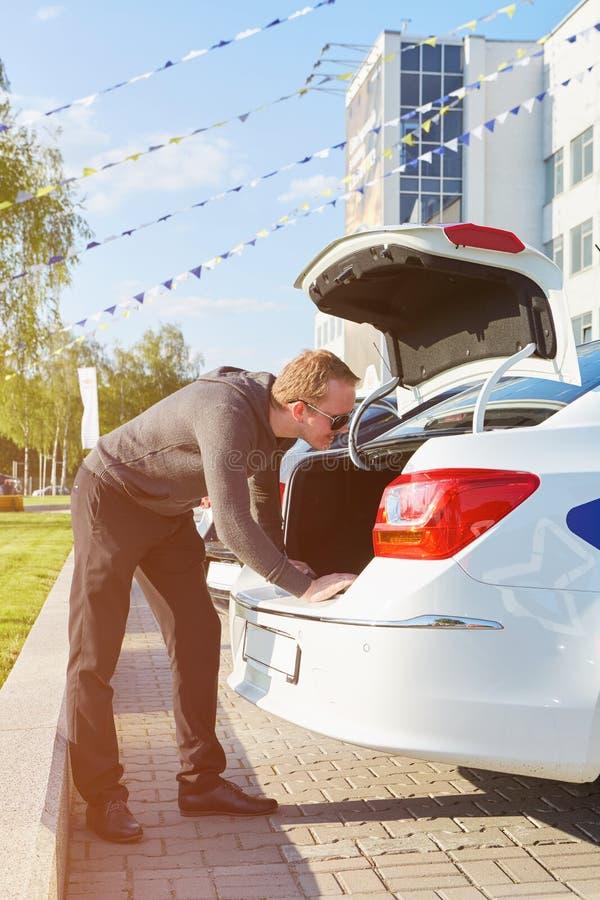 Boczny widok patrzeje w bagażnika samochodzie mężczyzna obrazy stock