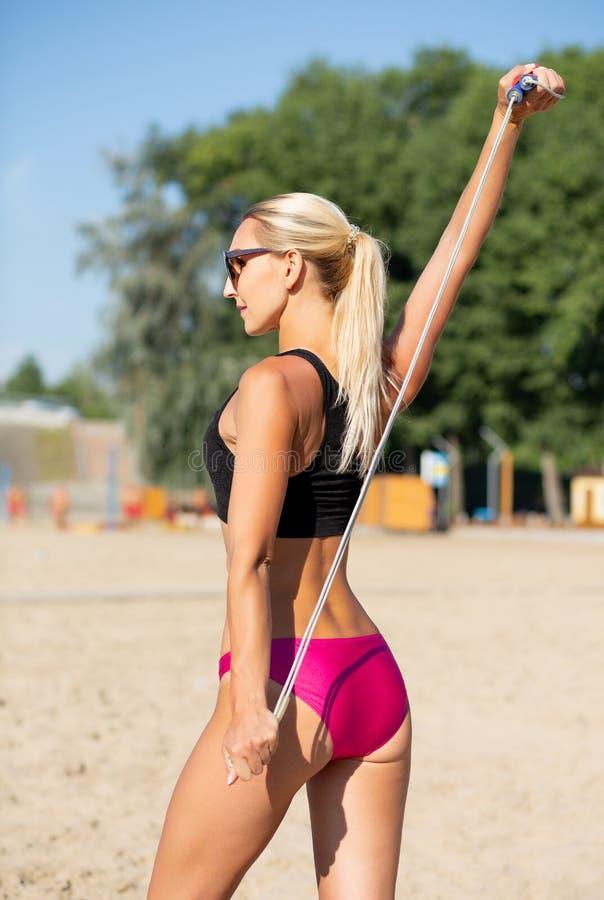 Boczny widok piękna dysponowana dziewczyna robi rozciąganiu opracowywa z skok arkaną przy plażą zdjęcia stock