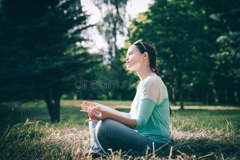 Boczny widok piękna kobieta medytuje w Lotosowej pozycji outdoors zdjęcie stock