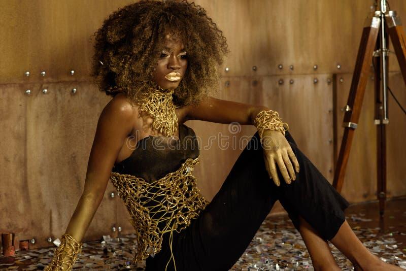 Boczny widok piękna młoda Afrykańska kobieta w złocistych akcesoriach i macaniu jej kolana podczas gdy siedzący na podłoga przeci obraz royalty free