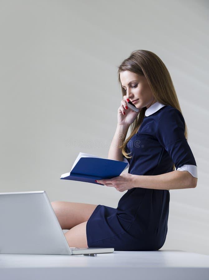 Boczny widok piękny i spokojny bizneswoman jest ubranym zmrok - błękit suknia, siedzi na jej biurku obrazy stock