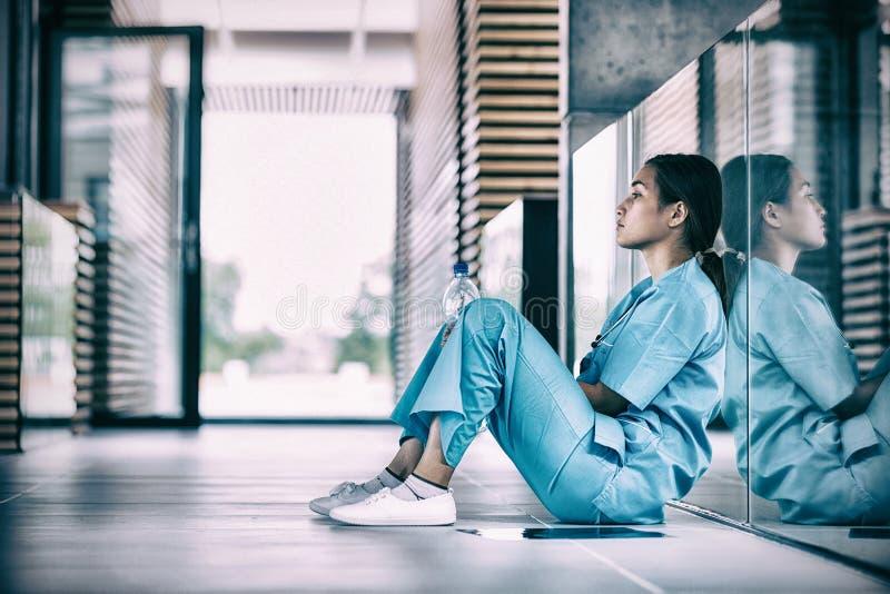 Boczny widok pielęgniarki obsiadanie na podłoga zdjęcie royalty free