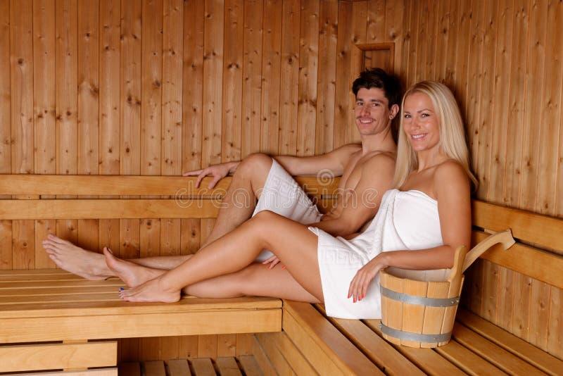 Potomstwo pary cieszy się sauna obrazy stock