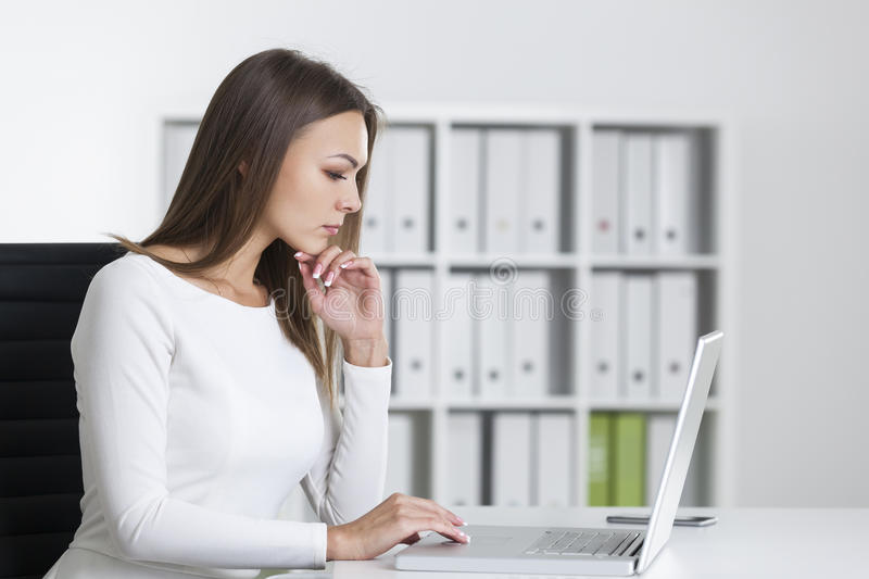 Boczny widok poważna kobieta przy laptopem obraz stock