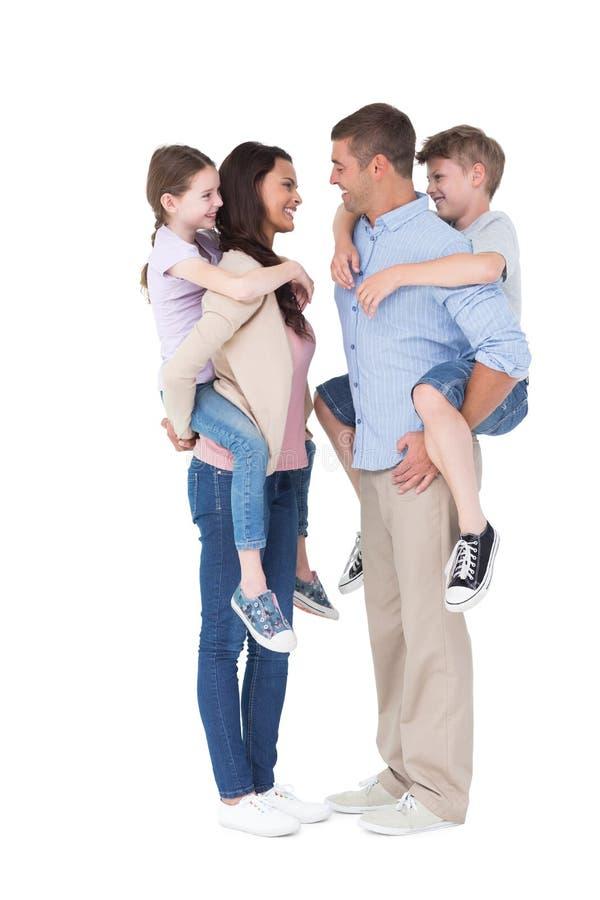 Boczny widok rodzice daje piggyback przejażdżce dzieci obrazy stock