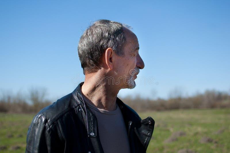 Boczny widok starszy przystojny mężczyzna jest ubranym czarną skórzaną kurtkę stoi outdoors w parku na niebieskiego nieba tle zdjęcie stock