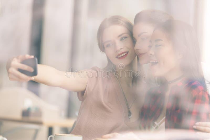 boczny widok szczęśliwi przyjaciele bierze selfie wpólnie zdjęcie stock