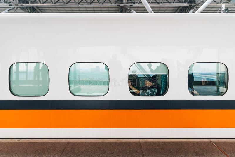 Boczny widok Tajwański Wysoki prędkości pociągu, bielu pociąg z lampasem z pasażerami siedzi blisko nadokiennej przerwy na platfo obrazy royalty free