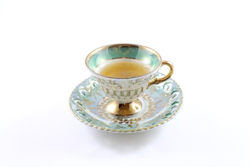 Boczny widok teacup i spodeczek z herbatą zieleni i biali zdjęcia royalty free