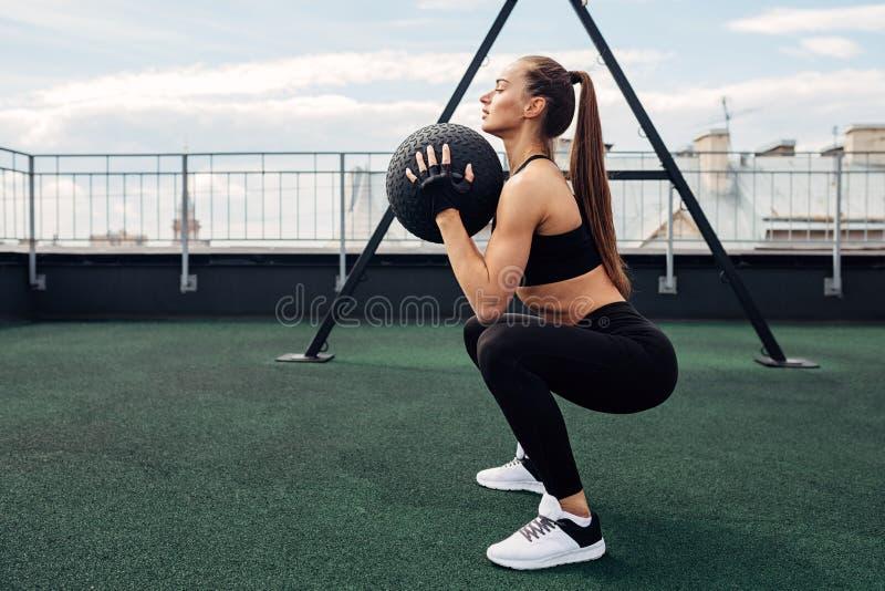 Boczny widok trzyma medycyny piłkę mięśniowa kobieta podczas gdy robić kuca zdjęcia royalty free