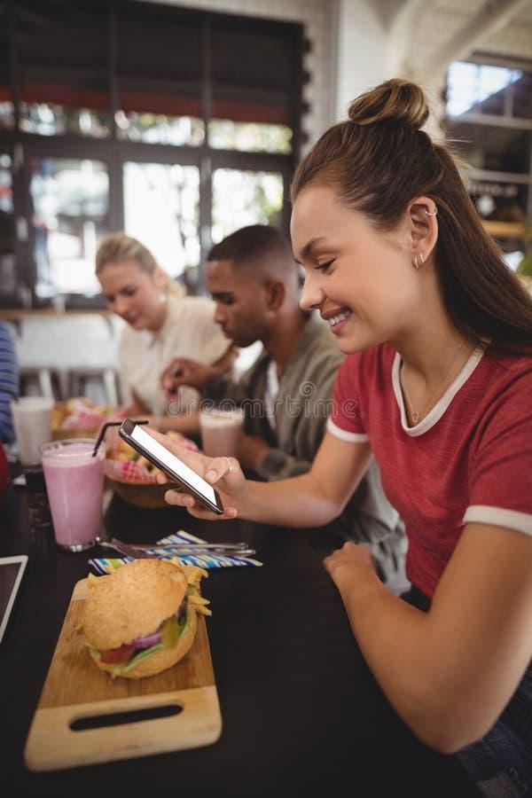Boczny widok uśmiechnięty młodej kobiety wysylanie sms podczas gdy siedzący z hamburgerem zdjęcie stock