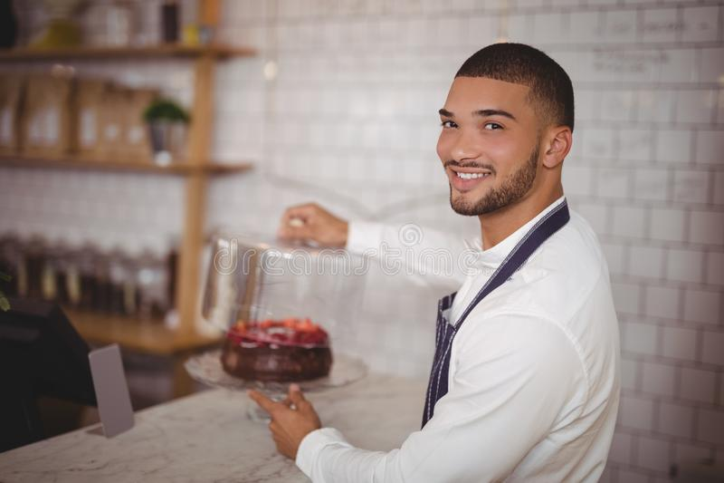 Boczny widok uśmiechnięty młody kelnera mienia tort przy kontuarem zdjęcia stock
