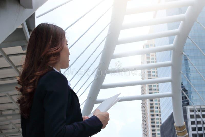 Boczny widok ufna młoda Azjatycka biznesowa kobieta z nutową pozycją posyłać dalekiego przy miastowym budynku miastem z c i patrz zdjęcie royalty free