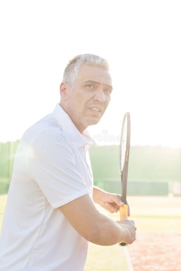 Boczny widok ufny dorośleć mężczyzny huśta się tenisowego kant na sądzie przeciw jasnemu niebu obraz stock