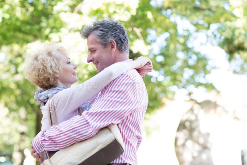 Boczny widok w średnim wieku pary obejmowanie podczas gdy patrzejący each inny w parku fotografia royalty free