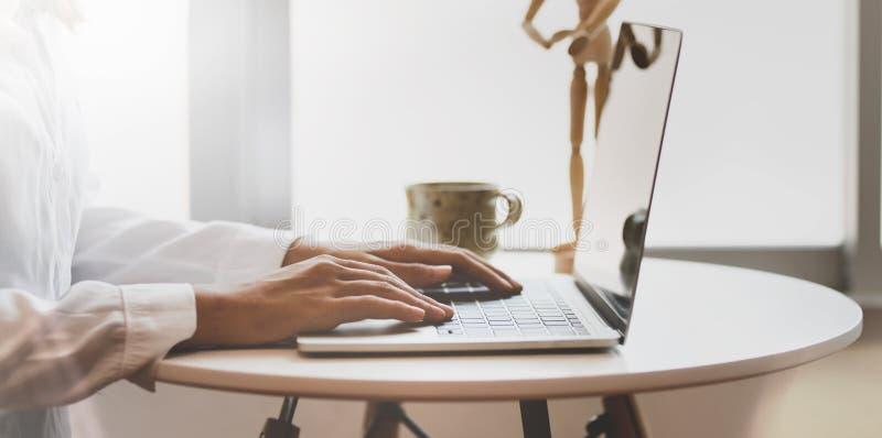 Boczny widok w górę żeńskiego pisarza ręki pisać na maszynie na laptopie zdjęcie royalty free