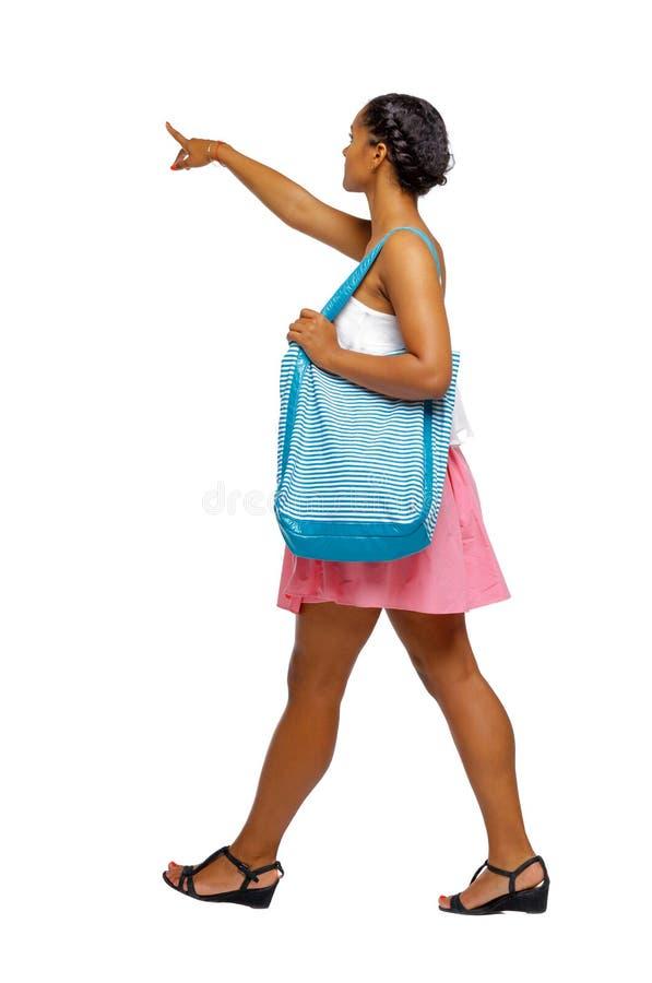 Boczny widok wskazywać afroamerykanina z plażową torbą który goe obraz stock