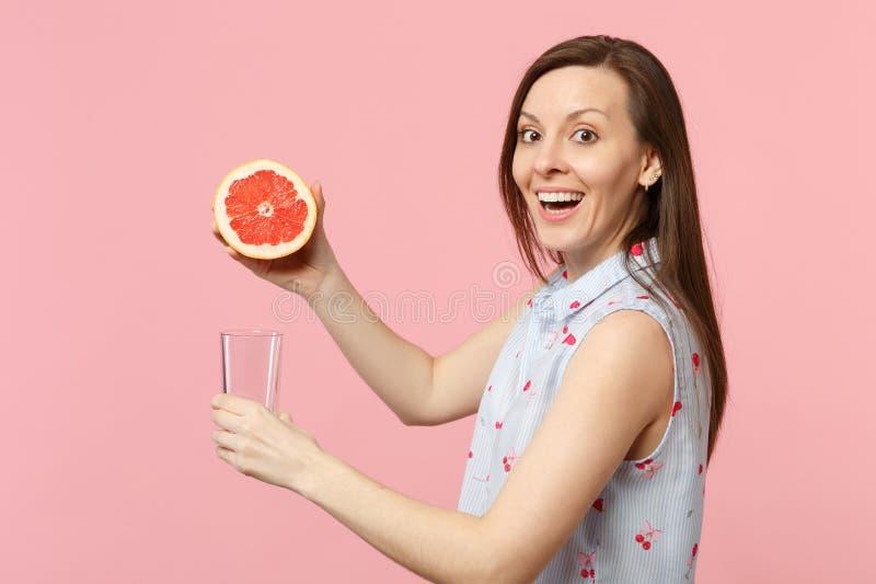 Boczny widok z podnieceniem młoda dziewczyna w lato odzieżowej trzyma połówce świeża dojrzała grapefruitowa szklana filiżanka na  obrazy stock