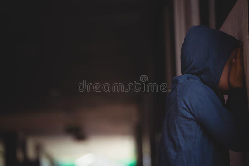 Boczny widok zakrywa jego twarz z rękami smutna chłopiec podczas gdy opierający na ścianie fotografia stock