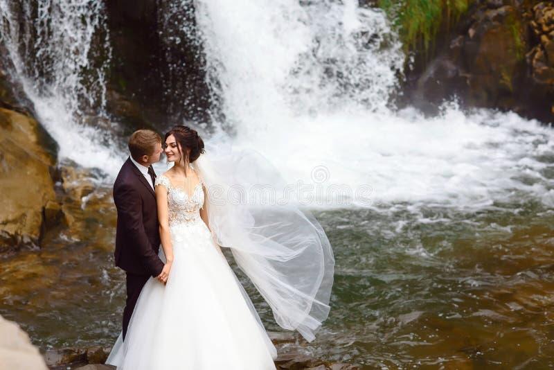 Boda, beso de los pares en colinas cerca de la cascada magnífica hermosa en montaña Viento que agita un velo largo Paisaje de col fotos de archivo