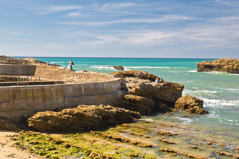 Boda de la novia y del novio que se colocan en roca en costa atlántica colorida escénica en cielo azul en Biarritz, país basque, foto de archivo libre de regalías