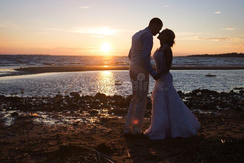 Boda de los pares de la historia de amor en el mar de la puesta del sol outdoor fotografía de archivo libre de regalías