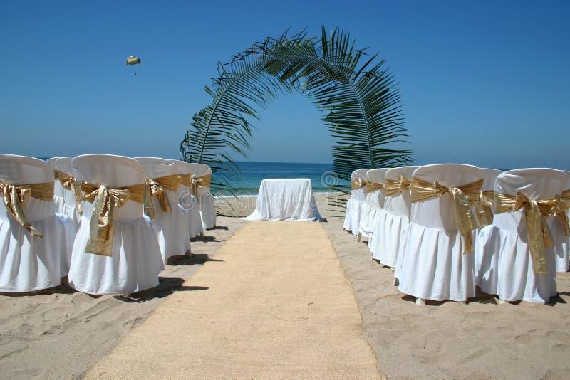 Boda de playa con las sillas, el arco de la palma y el océano en fondo imagen de archivo