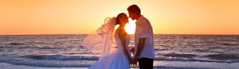Boda de playa de la puesta del sol de Married Couple Kissing de novia y del novio imagen de archivo libre de regalías