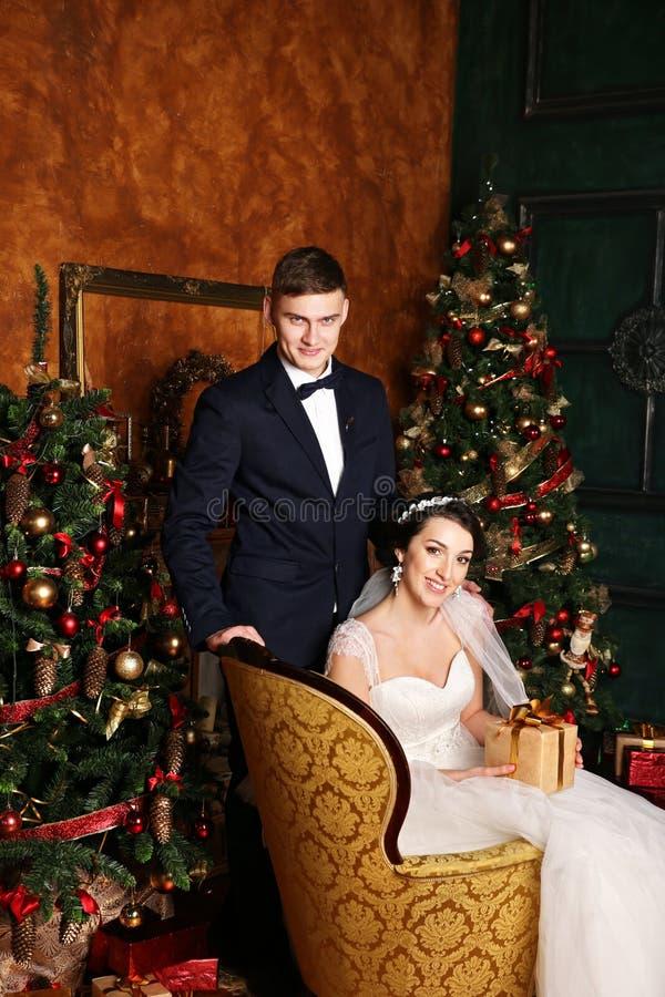 Boda del invierno Amantes novia y novio en la decoración de la Navidad Novio que sostiene el regalo Sorpresa romántica para la Na fotografía de archivo