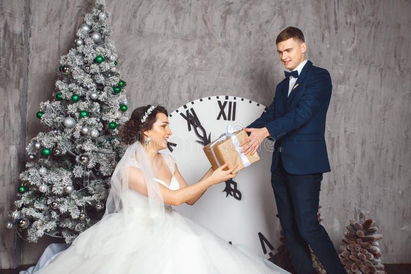 Boda del invierno Amantes novia y novio en la decoración de la Navidad Novio que sostiene el regalo Sorpresa romántica para la Na fotos de archivo