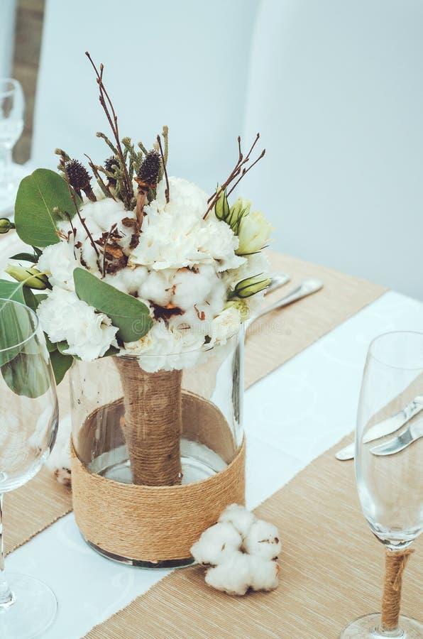 Boda del invierno con el cono, la decoración del algodón y el ramo nupcial blanco en sistema de la tabla Estilo rústico, claveles foto de archivo