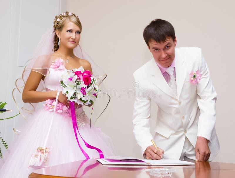 boda El novio firma los documentos del registro foto de archivo libre de regalías