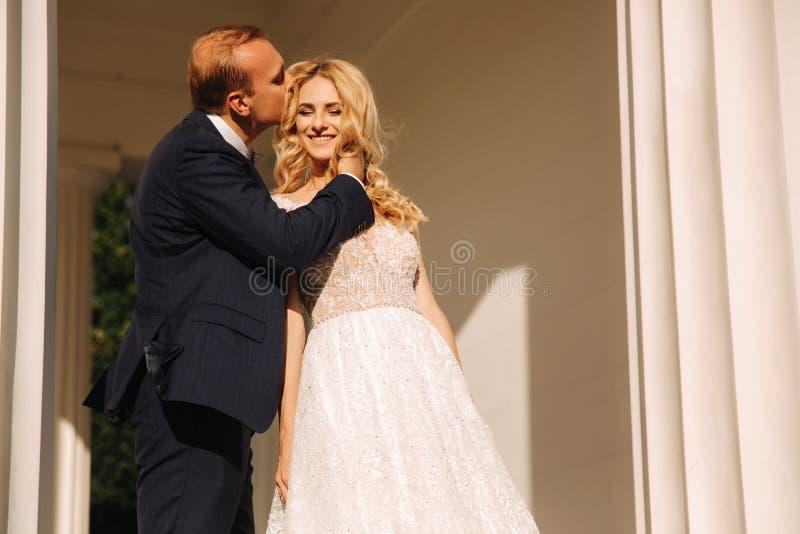 Boda en Grecia Los pares miran el uno al otro y sonrisa Ca?da de la novia del pelo rubio en amor fotos de archivo libres de regalías