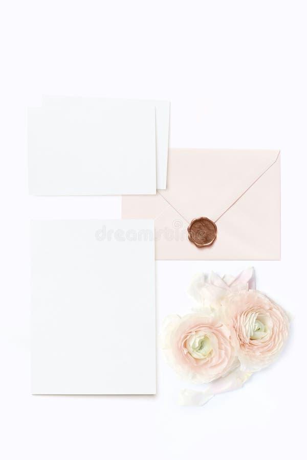 Boda femenina, maquetas de la mesa del cumpleaños Las tarjetas de felicitación en blanco, el sobre con el sello y el ranúnculo pe imagenes de archivo