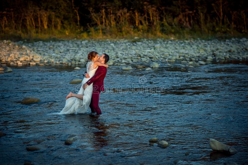 Boda horizontal tirada de los recienes casados hermosos El novio en traje rojo es que se besa y de elevación encima de su novia e fotografía de archivo