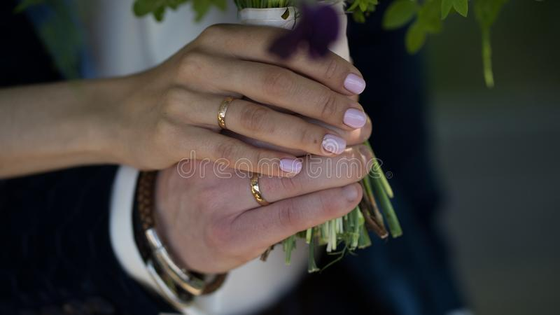 Boda, manos de los recienes casados con los anillos en sus fingeres imagenes de archivo