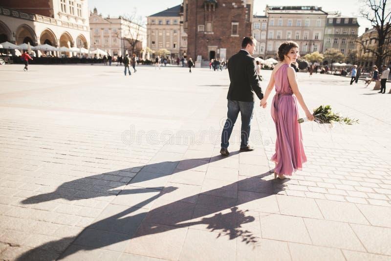 boda pares hermosos, novia con el vestido rosado que camina en la ciudad vieja Kraków, sus sombras fotos de archivo libres de regalías