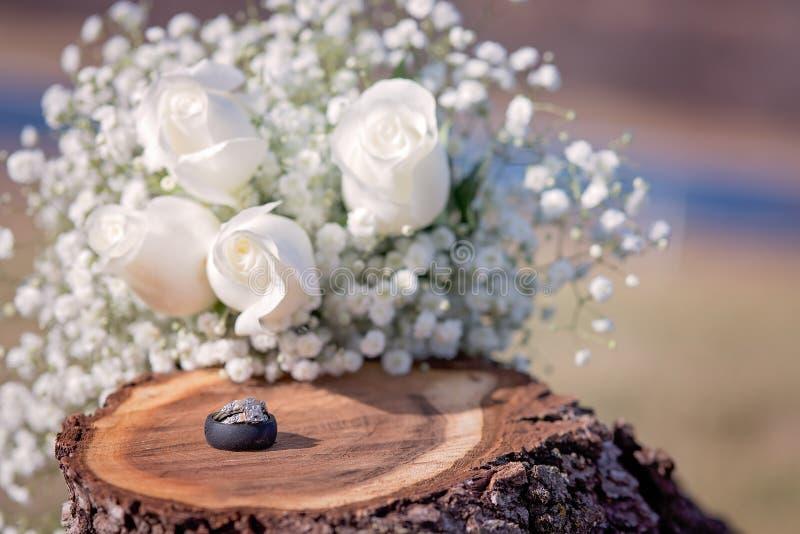 Boda y anillos de compromiso en tocón de madera con las rosas blancas fotos de archivo libres de regalías