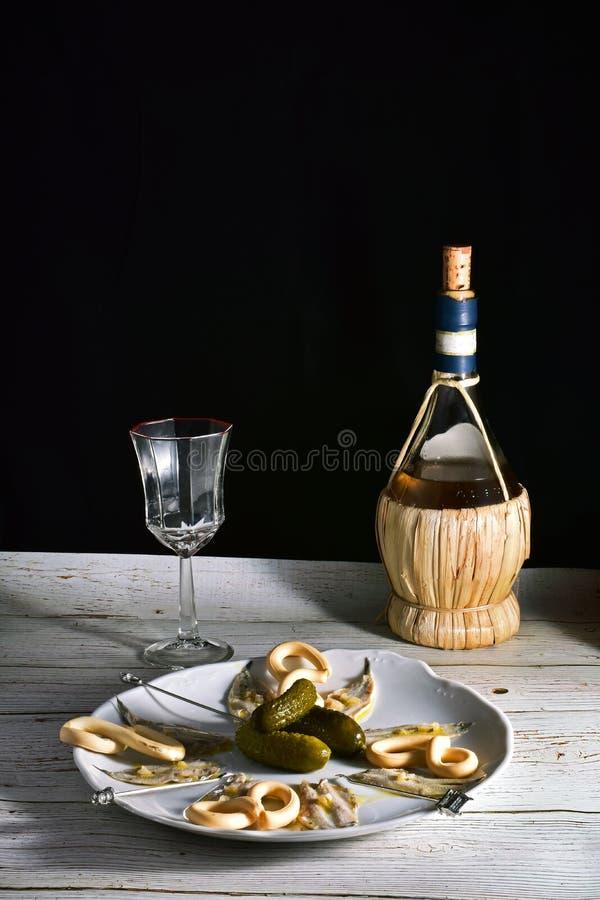 Bodegon avec le plat des anchois en vinaigre et vin photo libre de droits