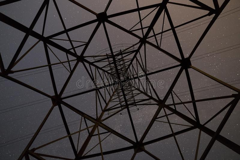 Bodem lage hoekige mening van mooie donkerblauwe sterrige hemel van binnenuit van hoogspanningstoren royalty-vrije stock afbeeldingen