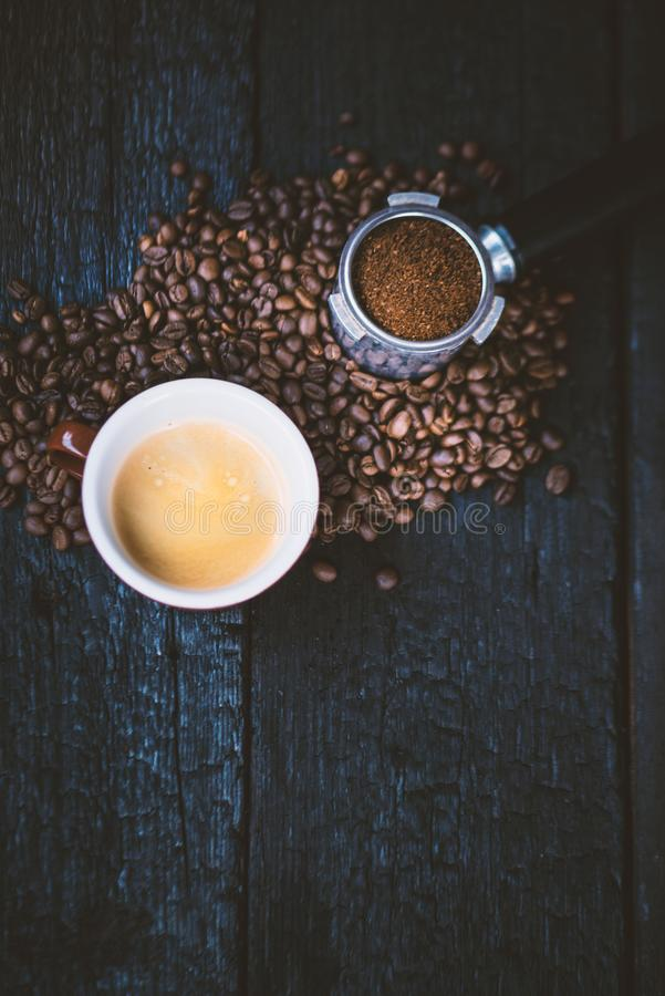 Bodemloze filter met malenbonen op een houten zwarte lijst en een kop van espresso De geroosterde Bonen van de Koffie Espresso ex royalty-vrije stock afbeeldingen