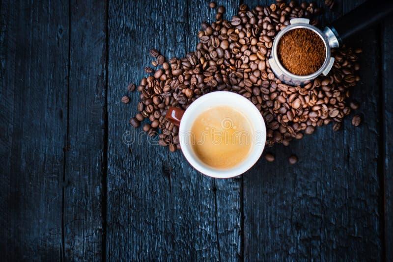 Bodemloze filter met malenbonen op een houten zwarte lijst en een kop van espresso De geroosterde Bonen van de Koffie Espresso ex stock afbeeldingen