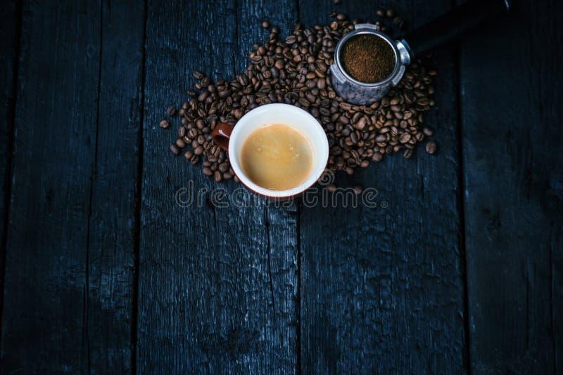 Bodemloze filter met malenbonen op een houten zwarte lijst en een kop van espresso De geroosterde Bonen van de Koffie Espresso ex royalty-vrije stock afbeelding
