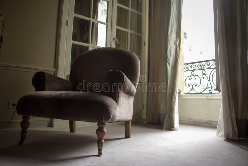 Bodemmening van een elegante grijze leunstoel over een venster met blinden in een historische flat op Plaats Vendome in Parijs stock afbeelding