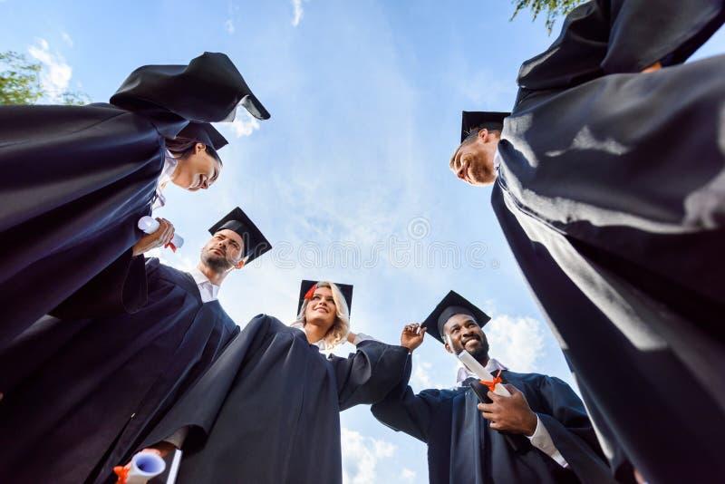 bodemmening van gelukkige jonge gediplomeerde studenten voor royalty-vrije stock afbeeldingen