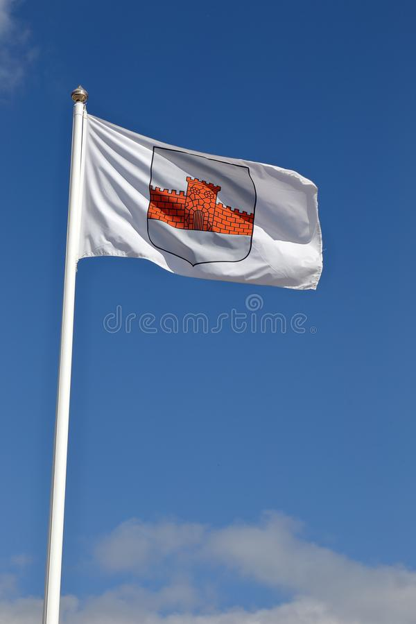 Boden municipality flag. Boden, Sweden - July 13, 2015: The flag with the coat of arms for the municipality of Boden hoisted on flag pole against the blue sky royalty free stock photos