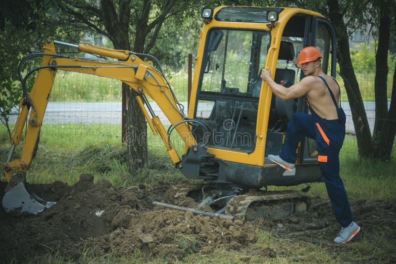 Bodenbewegungskonzept Bodenbewegungsbetreiber am Bagger Mannaufstieg auf Gräber für Bodenbewegung Bodenbewegung und Fundament stockbild