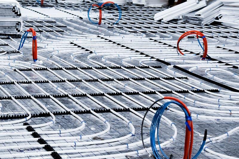 Bodenheizungssystem mit weißen Rohren während des Baus stockfotografie
