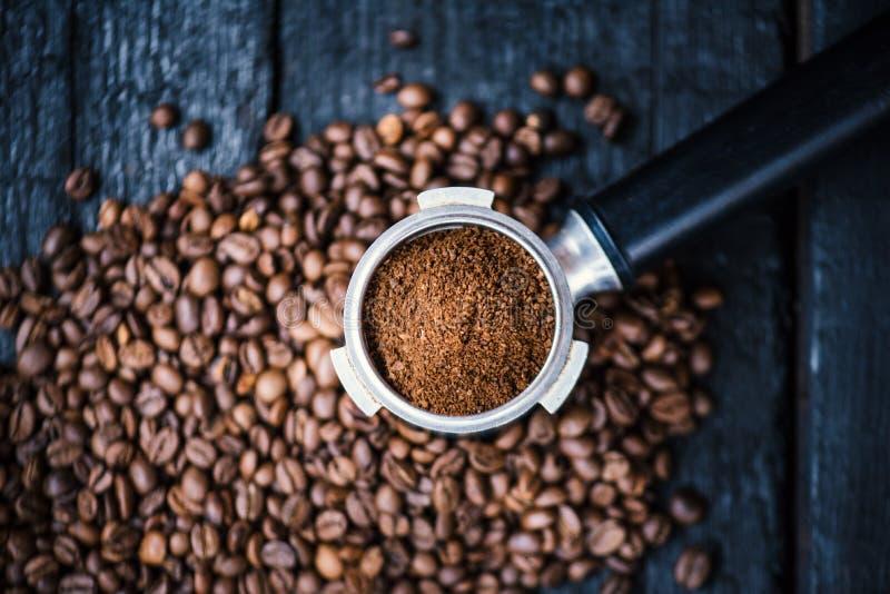 Bodenloser Filter mit Schleifenbohnen auf einer hölzernen schwarzen Tabelle Gebratene Kaffeebohnen Espressokaffeeextraktion Berei lizenzfreies stockfoto