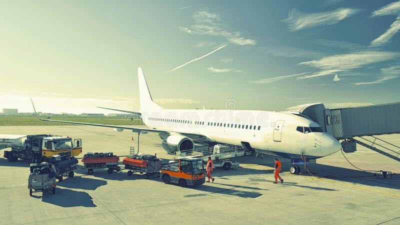 Bodenpersonal, das ein Flugzeug vor Abfahrt am airpor behandelt stockfotografie
